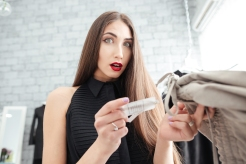Amazed woman holding price tag in clothing store and looking at camera